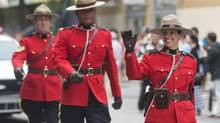 Members of the Royal Canadian Mounted Police (RCMP) wave to the crowd as they participate in the annual Canada Day parade in Montreal, Monday, July 1, 2013. (Graham Hughes/THE CANADIAN PRESS)