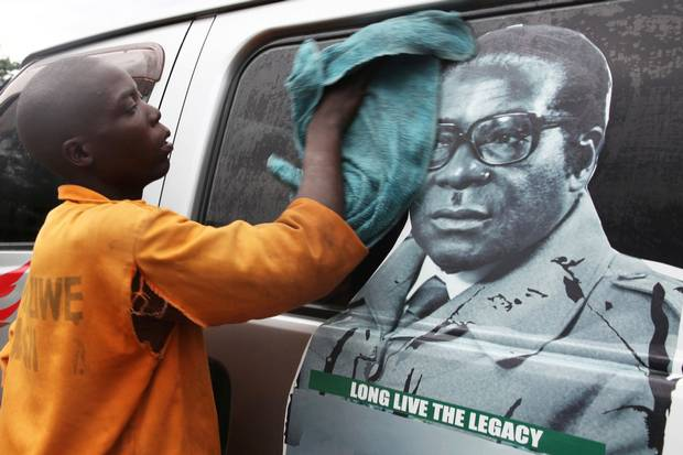 Nov. 15: A youth washes a minibus bearing Mr. Mugabe's portrait at a bus terminal in Harare.