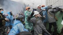 Anti-government protesters throw stones during clashes with riot police in Kiev's Independence Square, the epicenter of the country's current unrest, Kiev, Ukraine, Wednesday, Feb. 19, 2014. (Efrem Lukatsky/AP)