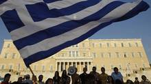 Protesters raise a Greek flag in front of parliament during a rally against austerity economic measures in Athens' Syntagma (Constitution) Square in this June 17, 2011 file photo. (JOHN KOLESIDIS/JOHN KOLESIDIS/REUTERS)