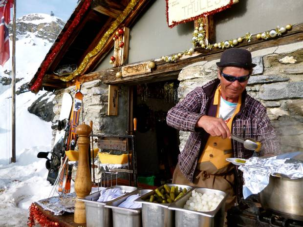 Thomas, manager of Cabane des Taules, prepares raclette outside a bare-bones shed; it's a popular location even without a formal patio.