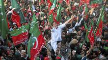 A supporter of political party Pakistan Tehreek-e-Insaf (PTI) shouts slogan as he waves the party flag with others during a rally in Karachi December 25, 2011. (AKHTAR SOOMRO/AKHTAR SOOMRO/REUTERS)