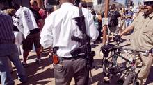 A man who supports the U.S. Constitution's Second Amendment right to keep and bear arms carries a military style AR-15 type rifle during a Obama opposition rally in Phoenix ealier this week. (Jack Kurtz)