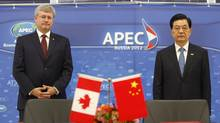 Prime Minister Stephen Harper waits with Chinese President Hu Jintao at a signing ceremony in Vladivostok, Russia, Sunday Sept. 9, 2012. (Adrian Wyld/The Canadian Press)