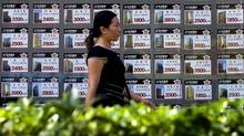 A woman walks past the properties price listings on display outside a real estate office in Beijing, Sept. 10, 2007. (ANDY WONG)