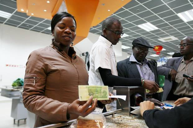 A customer holds a government-issued note that she received as change in a shop in Harare.