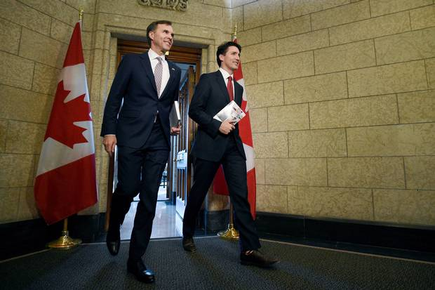 Finance Minister Bill Morneau and Prime Minister Justin Trudeau leave the Prime Minister's office holding copies of the federal budget in Ottawa on March 22, 2017.