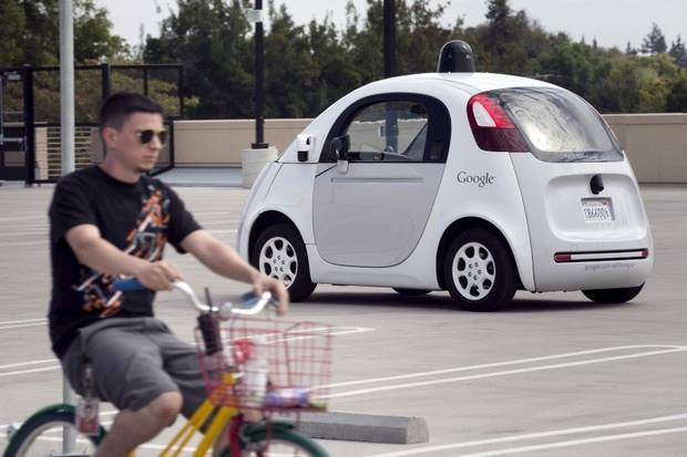 A Google employee on a bicycle acts as a real-life obstacle for a Google self-driving prototype car to react to during a media preview of Google's prototype autonomous vehicles in Mountain View, California, Sept. 29, 2015.