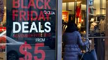 Shoppers walk past a Black Friday sale sign hanging in the window of H&M clothing store on Bloor Street in Toronto. (Deborah Baic/The Globe and Mail)