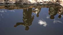 Libyan rebel fighters are reflected in a pool of oil on the outskirt of Brega, a major oil terminal on the Mediterranean coast, on Aug. 15, 2011. (GIANLUIGI GUERCIA/AFP/Getty Images)