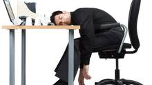 Businessman sleeping at desk (Photos.com/Getty Images)