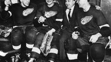 These happy Red Wings join coach Jimmy Skinner in their Detroit dressing room to celebrate their 3-2 victory over Toronto Maple Leafs in Stanley Cup semi-final series opener, in Detroit March 20, 1956. From left are Alex Delvecchio, Johnny Bucyk, Skinner and Gordie Howe. (THE ASSOCIATED PRESS)