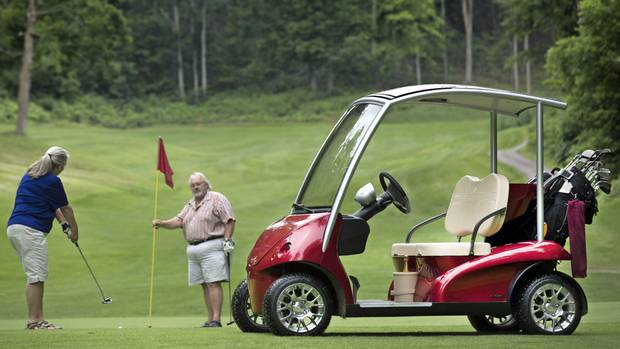 Rick and Anne Browne enjoy their community's private course in Burlington, Ontario on July 19, 2014. Mr. Browne's golf cart is high-end; equipped with, a mona other things, a small cooler, 12 volt power plug, windshield wipers, speedometer, sun roof, a wine cooler (with champagne in this case for Anne), and front and rear headlights. The suspension and steering are all far superior to a normal golf cart. (Peter Power for The Globe and Mail)