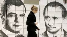 A woman walks by a panel made of cardboard boxes, displaying Russia�s President Dmitry Medvedev, left, and Prime Minister Vladimir Putin, at an innovation technologies exhibition in the city of Rostov-on-Don. (Stringer/Russia/REUTERS)