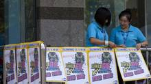 Employees of a Suning appliance shop puts up sales promotional posters outside a mall in Beijing, China, Wednesday, Aug. 15, 2012. (Alexander F. Yuan/AP)