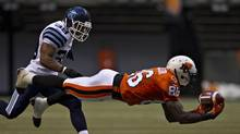 BC Lions wide receiver Courtney Taylor dives for a pass from quarterback Travis Lulay as Toronto Argonauts safety Matt Black (L) moves in during the first half of their CFL football game in Vancouver, British Columbia July 4, 2013. (ANDY CLARK/REUTERS)