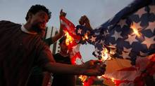 A Libyan follower of Ansar al-Shariah Brigades, burns the U.S. flag during a protest in front of the Tibesti Hotel, in Benghazi, Libya, Sept. 14, 2012, as part of widespread anger across the Muslim world about a film ridiculing Islam's Prophet Muhammad. (Mohammad Hannon/AP)