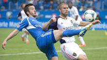 Montreal Impact's Jeb Brovsky, left, tackles Real Salt Lake's Chris Wingert during first half MLS soccer action in Montreal, Saturday, May 11, 2013. (Graham Hughes/THE CANADIAN PRESS)