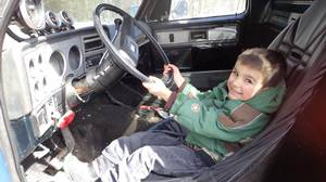 Lionel Smith's grandson tries the driver's seat of the 1978 Chevy on for size.