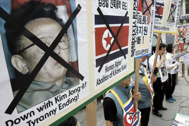 South Korean protesters hold pictures of North Korean leader Kim Jong-il and anti-North Korean banners during a rally near the U.S. embassy in Seoul on July 8, 2006.
