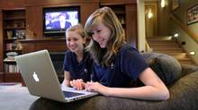 Taylor MacGillivary, right, and Jessica use a laptop to chat at Ashbury College in Ottawa. (Dave Chan for The Globe and Mail)