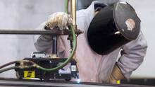 A worker cuts steel at the Irving shipyard in Halifax, on Friday, Oct. 19, 2012. (Andrew Vaughan/THE CANADIAN PRESS)