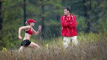 Coach Dave Scott-Thomas keeps an eye on the course as members of Guelph's Speed River track and field club work out. (Moe Doiron/The Globe and Mail)