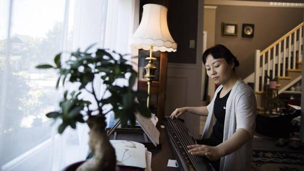 Anita He plays the guqin, a traditional Chinese instrument, at her home in Richmond.