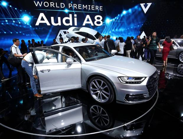 Attendees view the new Audi A8 after its presentation at the Audi Summit.