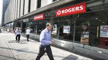 A man walks by a Rogers store in Toronto. (Gloria Nieto for The Globe and Mail)