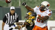 British Columbia Lions' Geroy Simon (R) has a pass knocked away by Edmonton Eskimos' Rod Williams during their CFL game in Edmonton September 22, 2012. (DAN RIEDLHUBER/REUTERS)