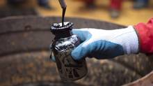 A worker collects crude oil sample at an oil well operated by Venezuela's state oil company PDVSA in Morichal July 28, 2011. (Carlos Garcia Rawlins/Carlos Garcia Rawlins/REUTERS)