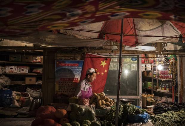 An ethnic Uyghur shopkeeper works next to a Chinese flag at his shop on June 29, 2017 in the old town of Kashgar, in the far western Xinjiang province, China.