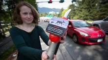 Emily Kelsall displays a gas pump nozzle with an environmental warning sticker she developed, as traffic passes by at the north end of the Lions Gate Bridge in North Vancouver, B.C., on May 9, 2014. (Darryl Dyck for The Globe and Mail)