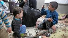 The children of Abdel Salam, a Syrian rebel brigade commander, play with the fragments of rocket-propelled grenades recently fired at their father's men. (Graeme Smith/The Globe and Mail/Graeme Smith/The Globe and Mail)