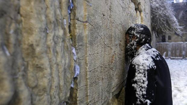 A man prays at the Western Wall in Jerusalem's Old City during a snowstorm on Dec. 13, 2013. (DARREN WHITESIDE/REUTERS)