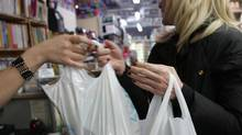A customer receives plastic biodegradable plastic bags when shopping at Noah's Natural Foods on Yonge St., Toronto.