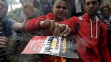 Students of Ain Shams University set fire to the 2013 draft constitution book at the university in Cairo December 18, 2013. Egyptians will vote on a new constitution on Jan. 14 and 15, pushing on with the army-backed government's plan for transition back to democracy. (STRINGER/REUTERS)