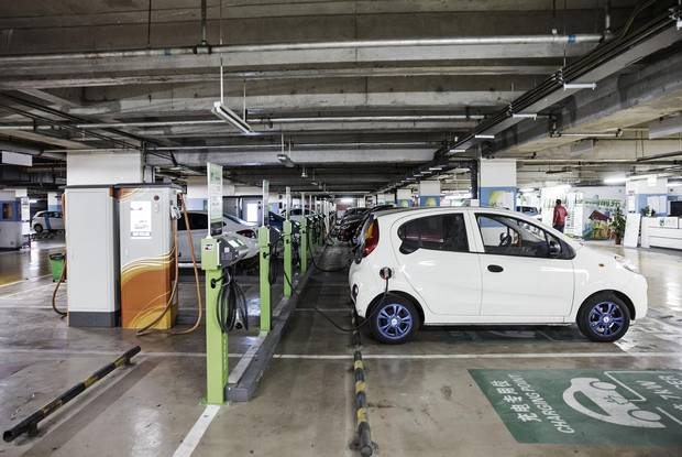 Electric automobiles sit connected to a charging station operated by Tellus Power Inc. at an underground parking lot in Beijing.