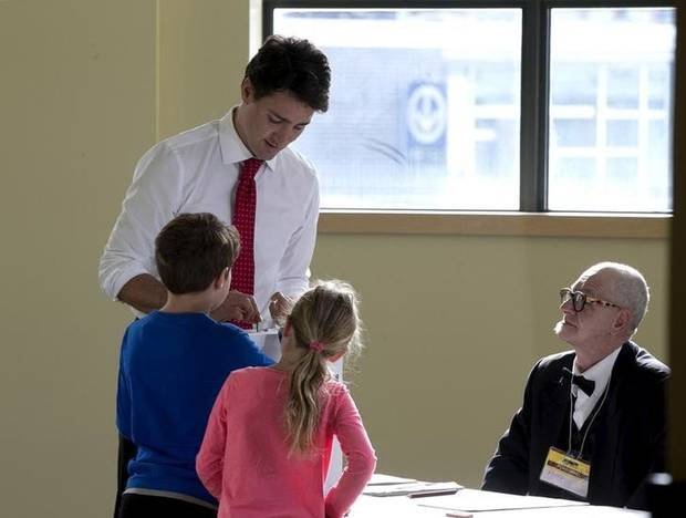 Liberal leader Justin Trudeau casts his ballot at the polling station as his son Xavier and daughter Ella-Grace watch in Montreal, Quebec, October 19, 2015.