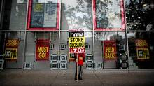 An employee holds a sign announcing a closing down sale outside the HMV Megastore on the corner of Burrard Street and Robson Street in Vancouver , Dec. 18, 2011. (Rafal Gerszak for The Globe and Mail/Rafal Gerszak for The Globe and Mail)