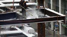 A construction worker sweeps snow from iron beams on a building site at Bay and Adelaide in Toronto Feb. 6, 2014. (CHRIS HELGREN/REUTERS)