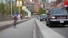 Cyclists make their way over the Burrard Bridge bike lane Sunday afternoon. The bike lane has had over one million riders in less than a year, an estimated 200,000 more bicycle trips than without the lanes in place. (Brett Beadle/The Globe and Mail/Brett Beadle/The Globe and Mail)