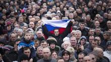 A man holds the Russian flag amid a large demonstration outside the regional government building in Donetsk, in the eastern Ukraine, March 9, 2014. The pro-Russian leader of Crimea's regional Parliament urged Ukraine Sunday to withdraw its roughly 3,500 troops stationed in the peninsula, as more Russian military units arrive there by the day. (URIEL SINAI/NYT)