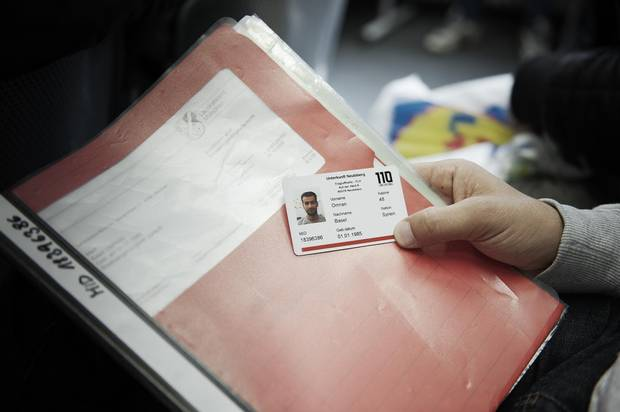 Basel Omran holds his paperwork and an ID card issued by the security service at his German refugee camp.