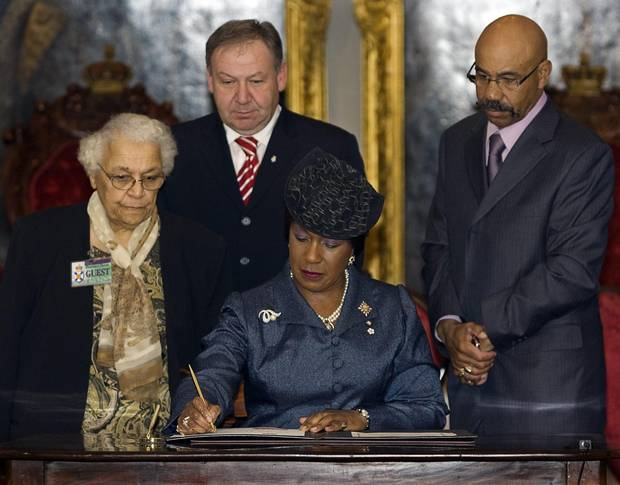Nova Scotia lieutenant-governor Mayann Francis signs the official pardon for Viola Desmond as her sister Wanda Robson, left, premier Darrell Dexter and Percy Paris, minister of African Nova Scotian Affairs, look on at a ceremony at the legislature in Halifax on April 15, 2010.