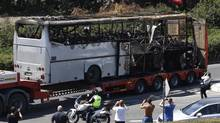 A truck carries a bus, that was damaged in a bomb blast in July 2012, outside Burgas Airport, about 400km (248 miles) east of Sofia in this July 19, 2012 file photo. (STOYAN NENOV/REUTERS)