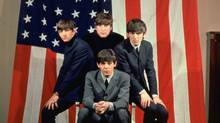 FILE PHOTO: The Beatles, clockwise from top center, John Lennon, George Harrison, Paul McCartney and Ringo Starr, pose with an American flag in a Paris photo studio prior to their first visit to the United States in January 1964. Thirty years after breaking up, and 20 years after John Lennon was shot dead, the Beatles' current popularity proves the sheer power of a musical legacy that dwarfs anything that's come after them. (Associated Press)