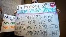 A woman holds a sign before a group of protesters delivered a petition seeking an inquiry into the death of Lucia Vega Jimenez to the Canadian Border Services Agency in Vancouver on Feb. 5, 2014. (Darryl Dyck for The Globe and Mail)
