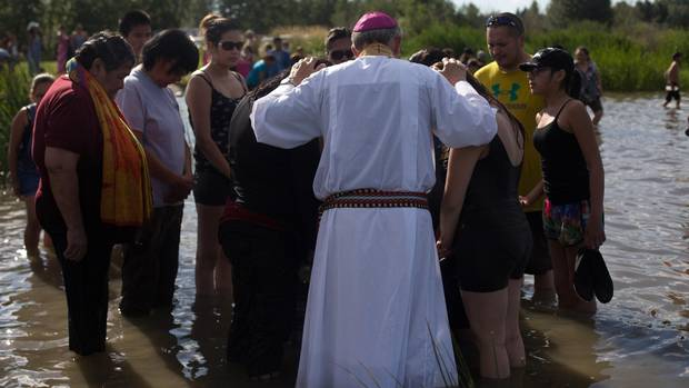 Father Sylvain Lavoie prays with believers in Lac Ste Anne, Alberta on Sunday, July 19, 2015.